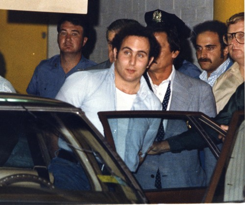 "Police officials surround David Berkowitz, 24, of Yonkers outside Brooklyn's 84th Precinct after his arrest as the ""Son of Sam"" killer early Thursday, Aug. 11, 1977. Photo courtesy of the Journal News."