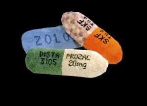 "Laura Splan, Prozac, Thorazine, Zoloft, 2000, latch hook on canvas, polyester filling, 11""x36""x11"""