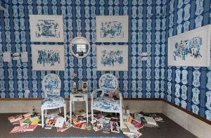 Photo of Art Installation titled Beyond a Room of One's Own from the SHE exhibition at ArtsWestchester in 2016. Colors are blue and white with Victorian era chairs and books scattered on the floor, framed pictures of famous women of world history.