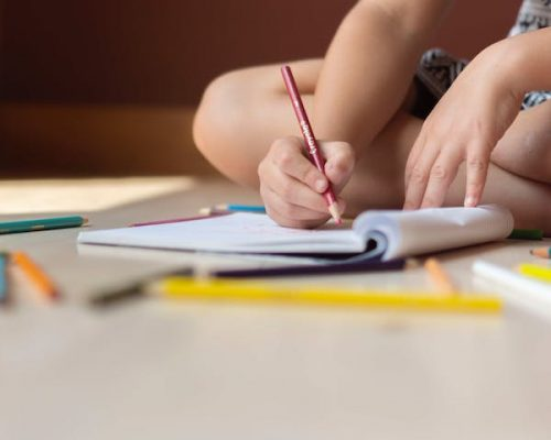A child coloring into a notebook.