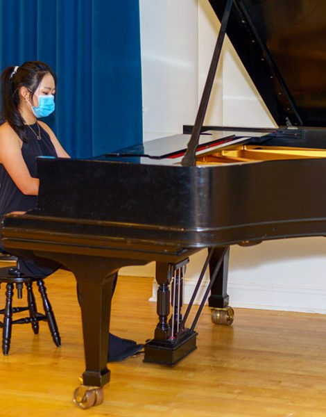 A student wearing a mask plays a piano at one of Hoff-Barthelson's student recitals